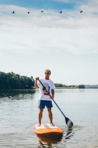Summer at Clemson - Young man paddleboarding