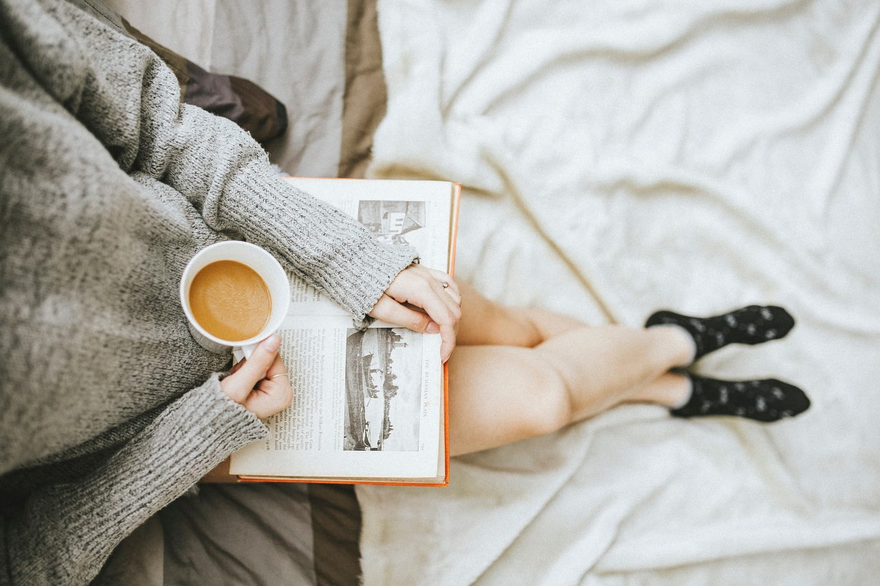 Girl sitting with coffee and a book