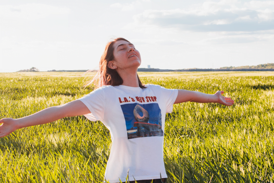 Girl standing in field smiling with arms out