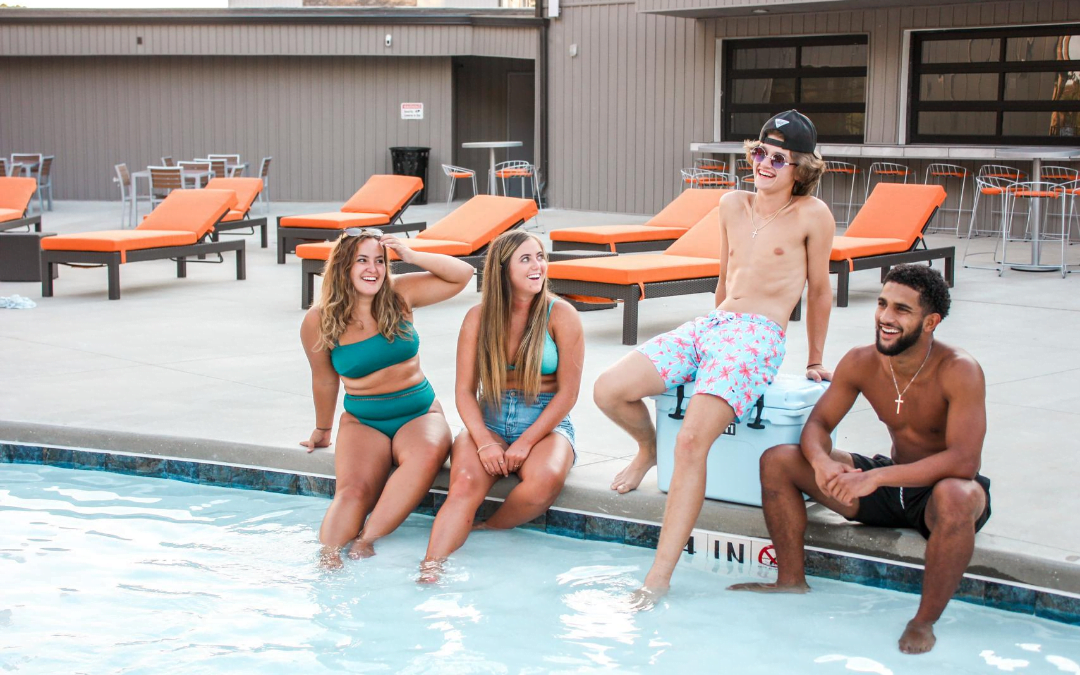 College students sitting at a pool